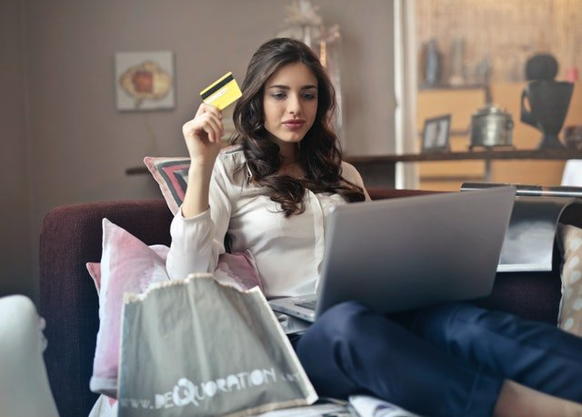 Woman holds up credit card with laptop on couch | Photo: Pxels