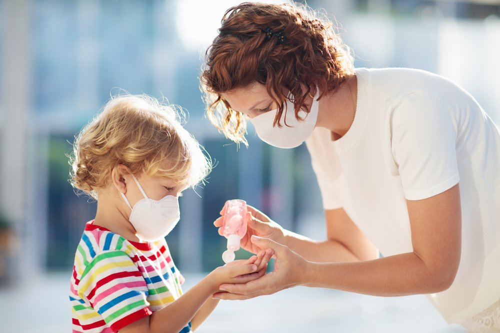 A child being given hand sanitizer while wearing a facemask during the coronavirus pandemic | Photo: Shutterstock/FamVeld