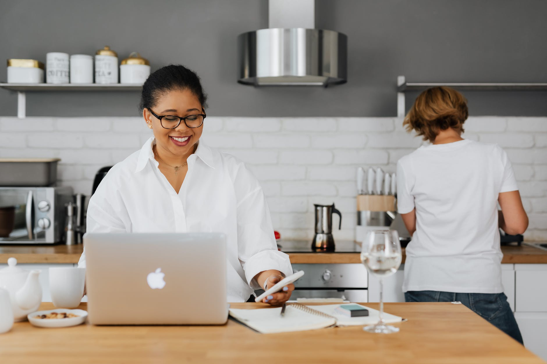 A smiling woman holding a cellphone and working on her laptop on a kitchen counter | Source: Pexels