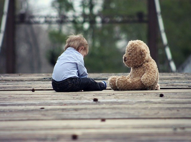A little boy sits next to a teddy bear | Photo: Pixabay