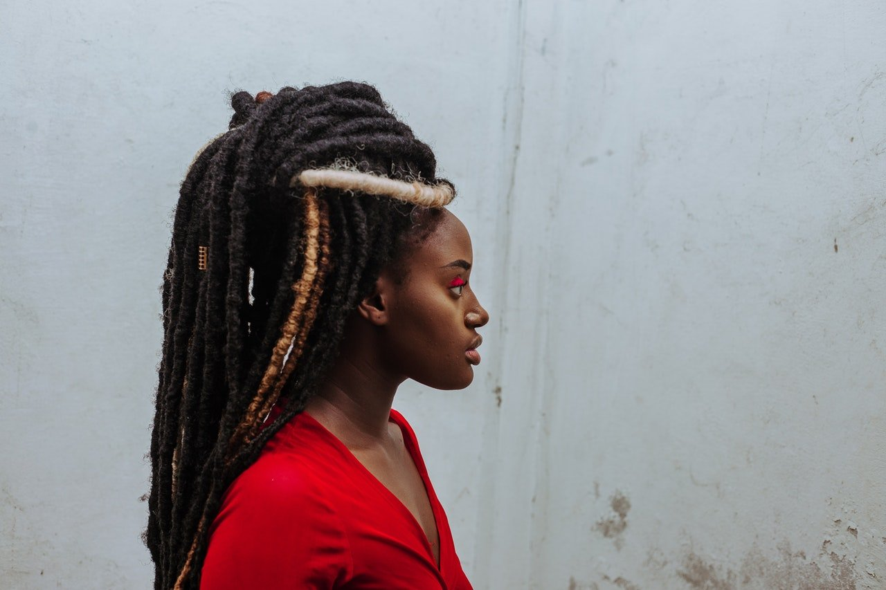 Photo of a young black woman with dreads looking away | Photo: Pexels