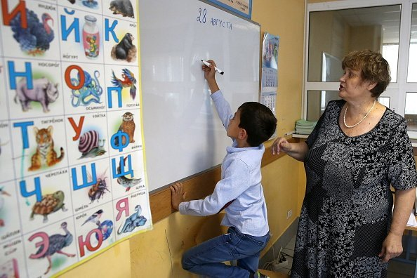 A young student and a teacher during a Russian Language class at an integration center of the Civic Assistance Committee | Photo: Getty Images