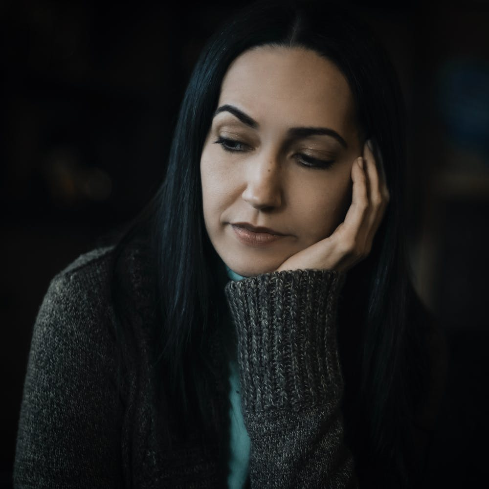 Woman wearing gray sweater, deep in thought. | Photo: Pexels