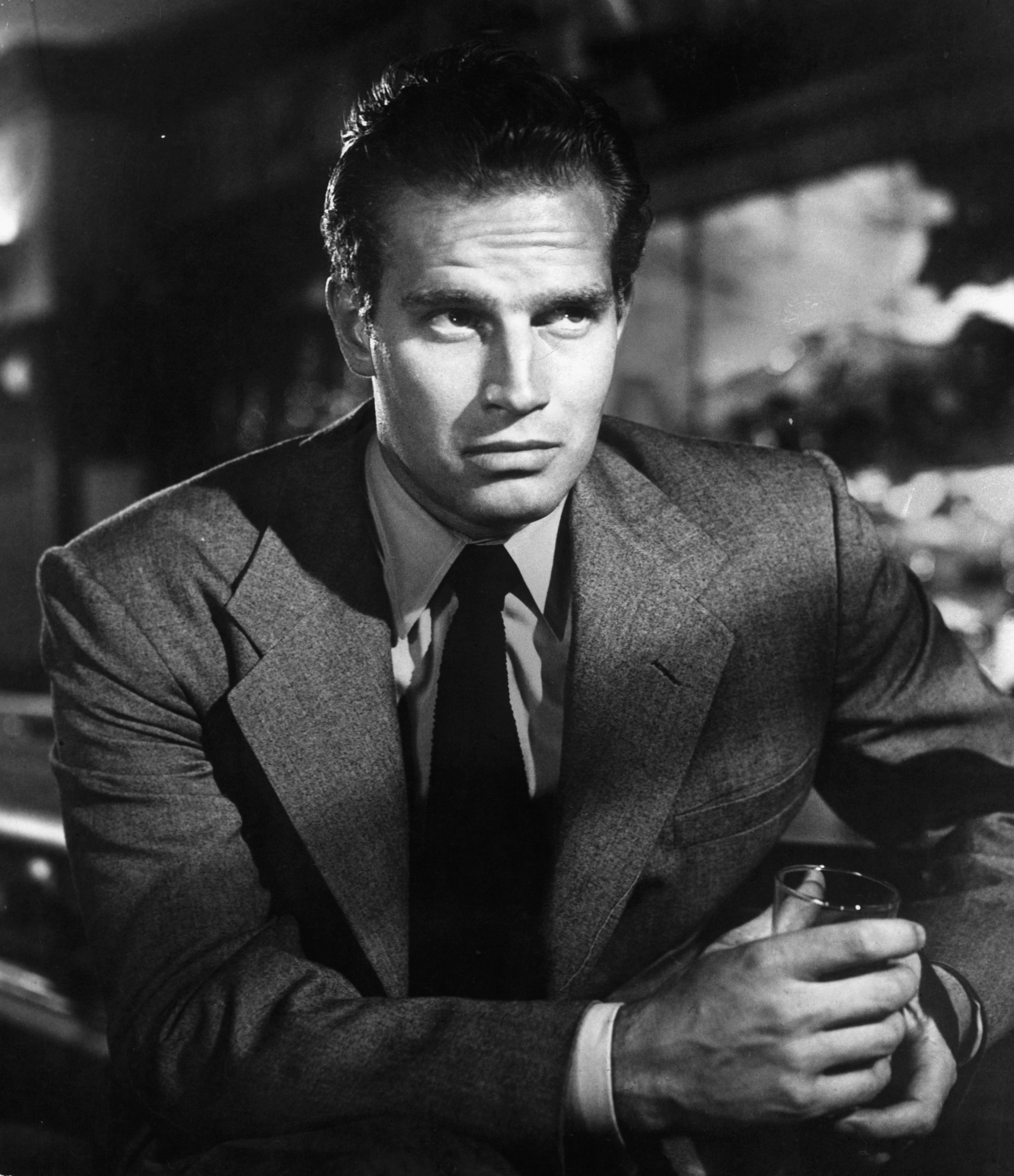 A photo of Charlton Heston holding a drink in a scene from the film 'Dark City', 1950 | Photo: Getty Images
