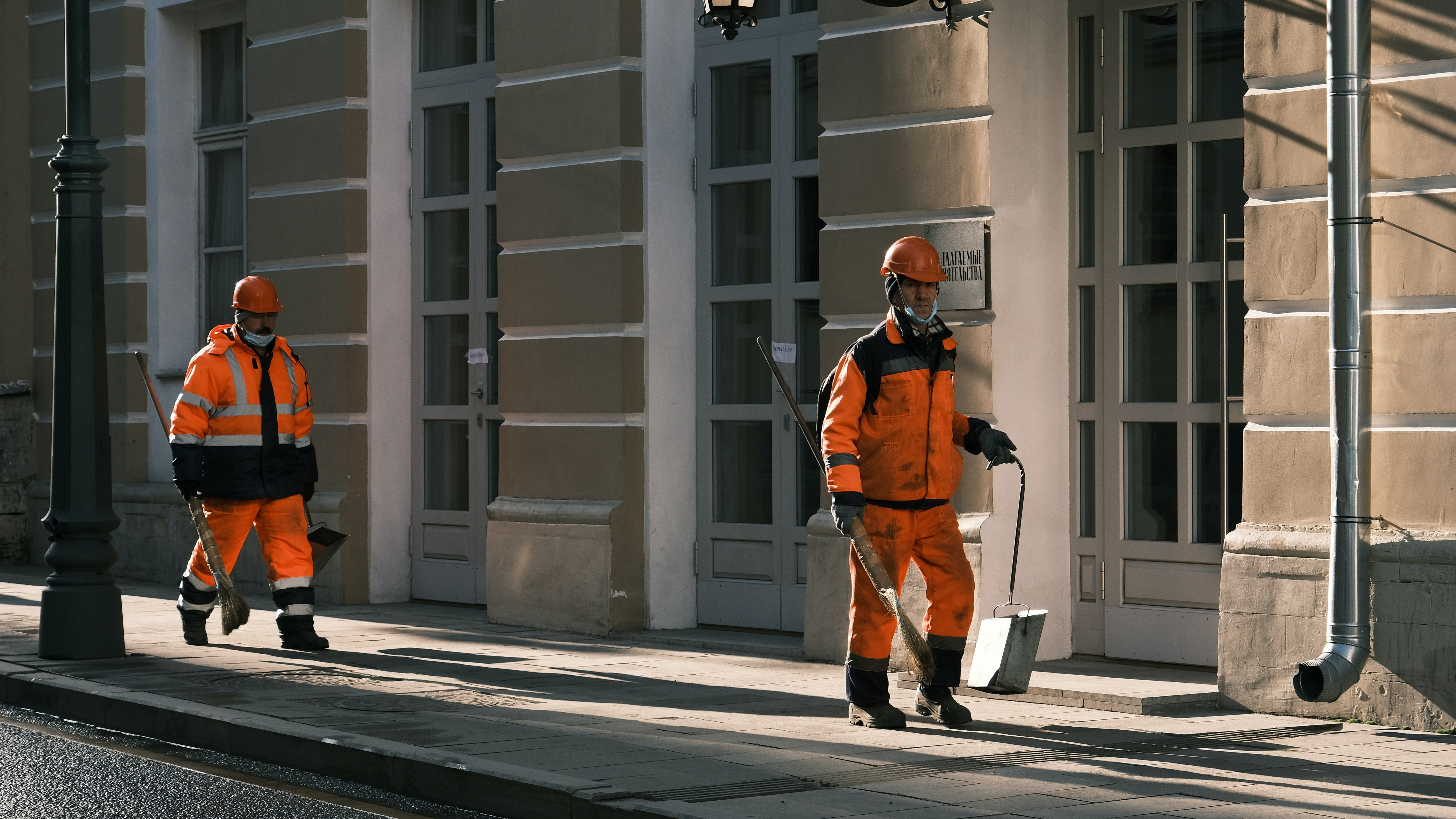Two janitors are seen walking along the road in the midst of fulfilling their duties   Photo: Pexels/Алексей Васильев