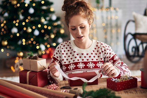 Woman tying ribbon on Christmas present | Photo: Getty Images