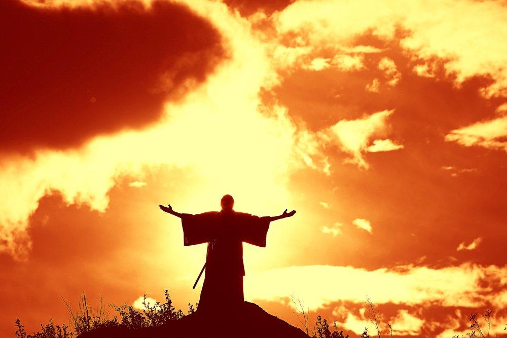 Silueta de hombre rezando en la montaña.| Fuente: Shutterstock