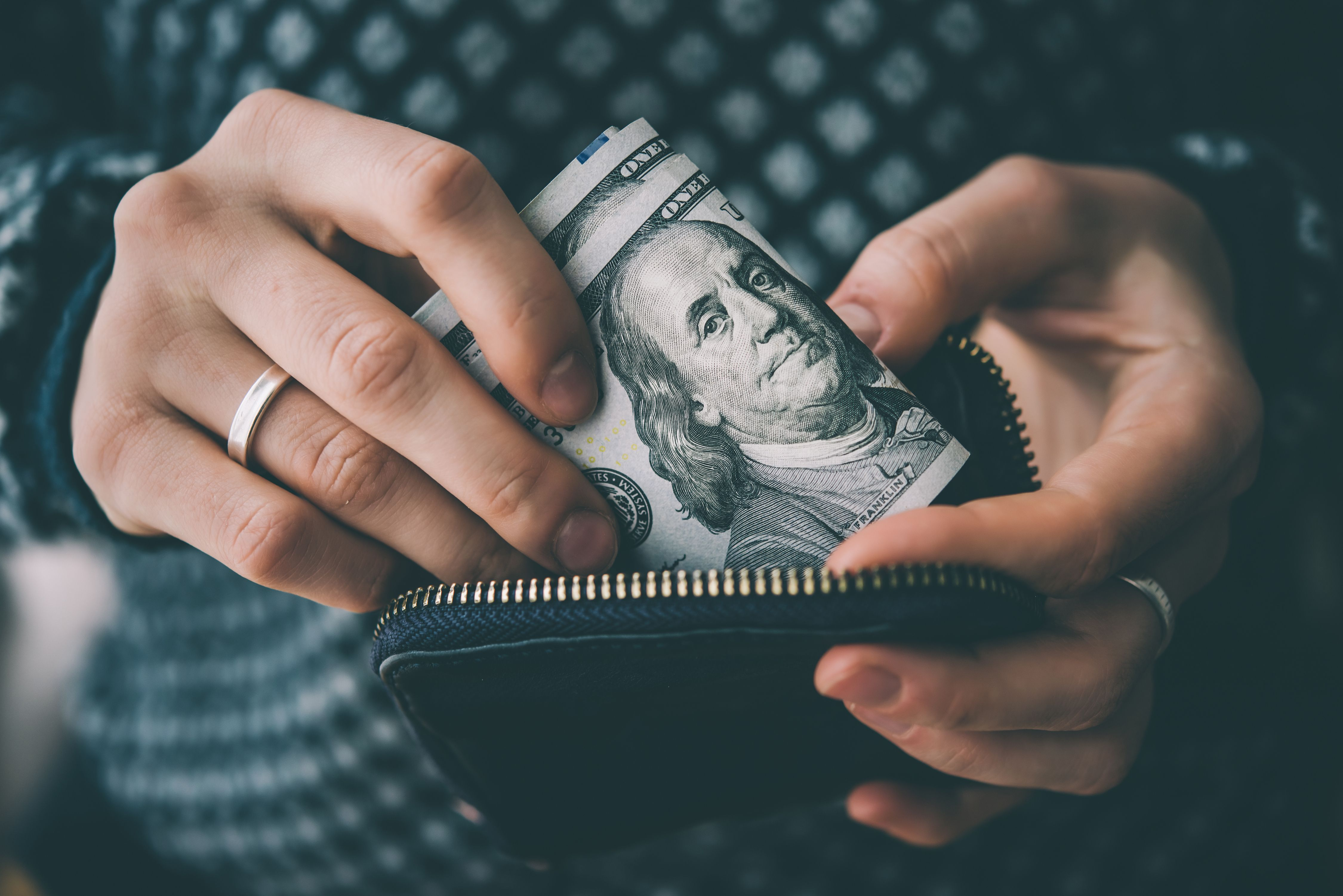 An individual putting dollar notes in their wallet. | Source: Shutterstock
