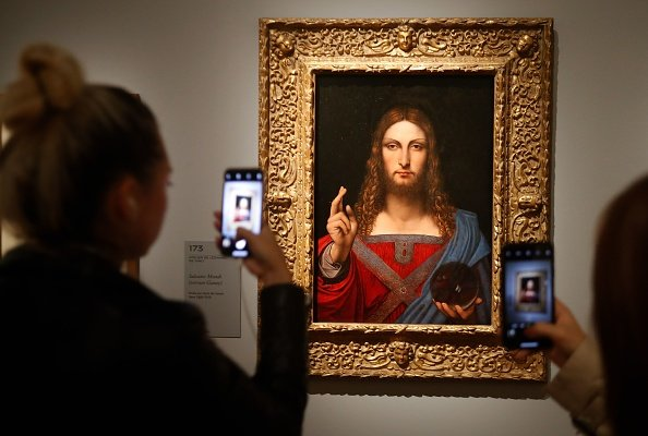 """People take pictures with mobile phone at an oil painting by Leonardo da Vinci's """"Salvator Mundi"""" on October 22, 2019 at the Louvre museum in Paris. 