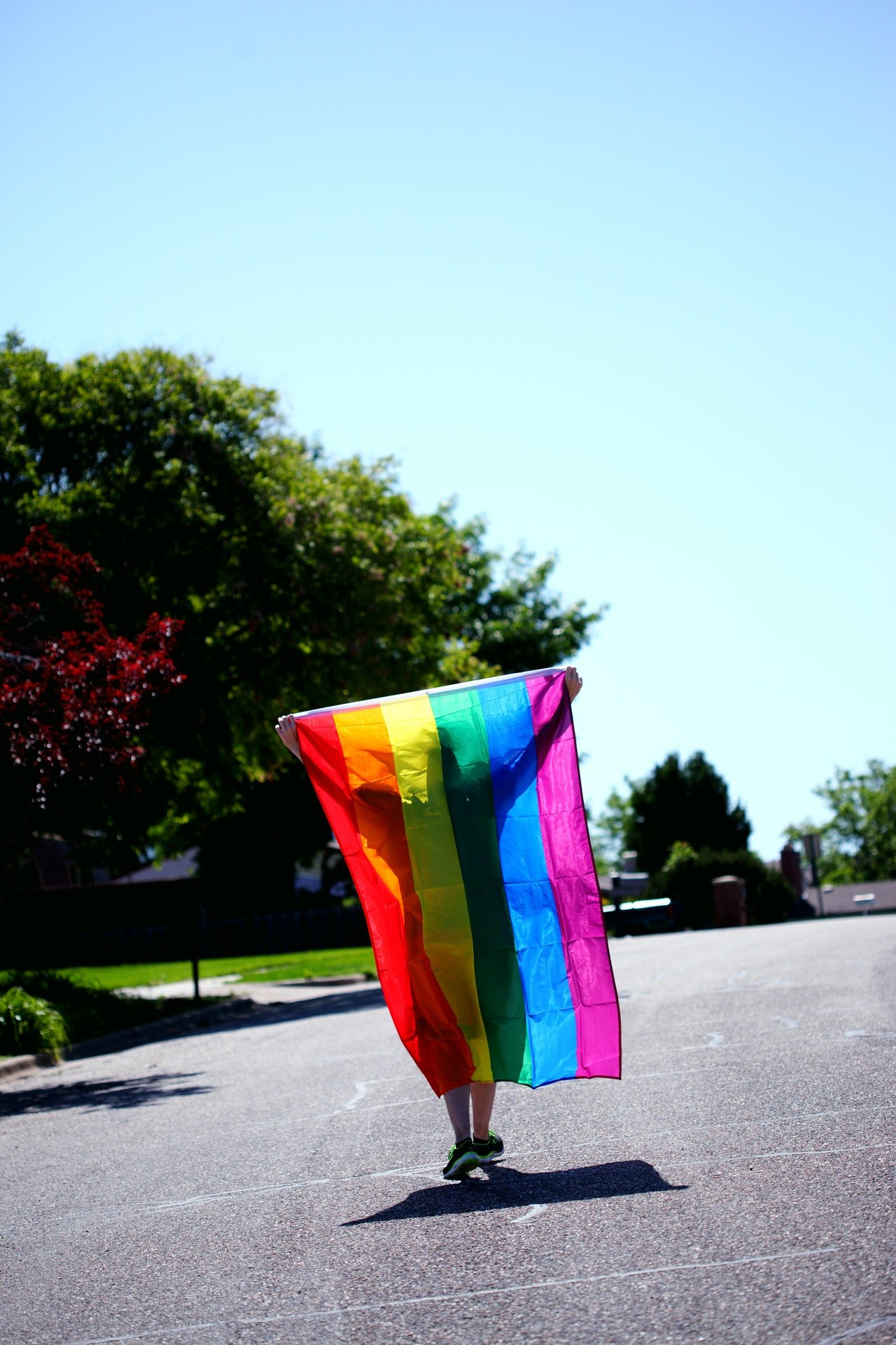 Photo of a person holding a rainbow flag | Photo: Pexels