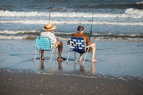 Two men fishing from the shore. | Source: Shutterstock.