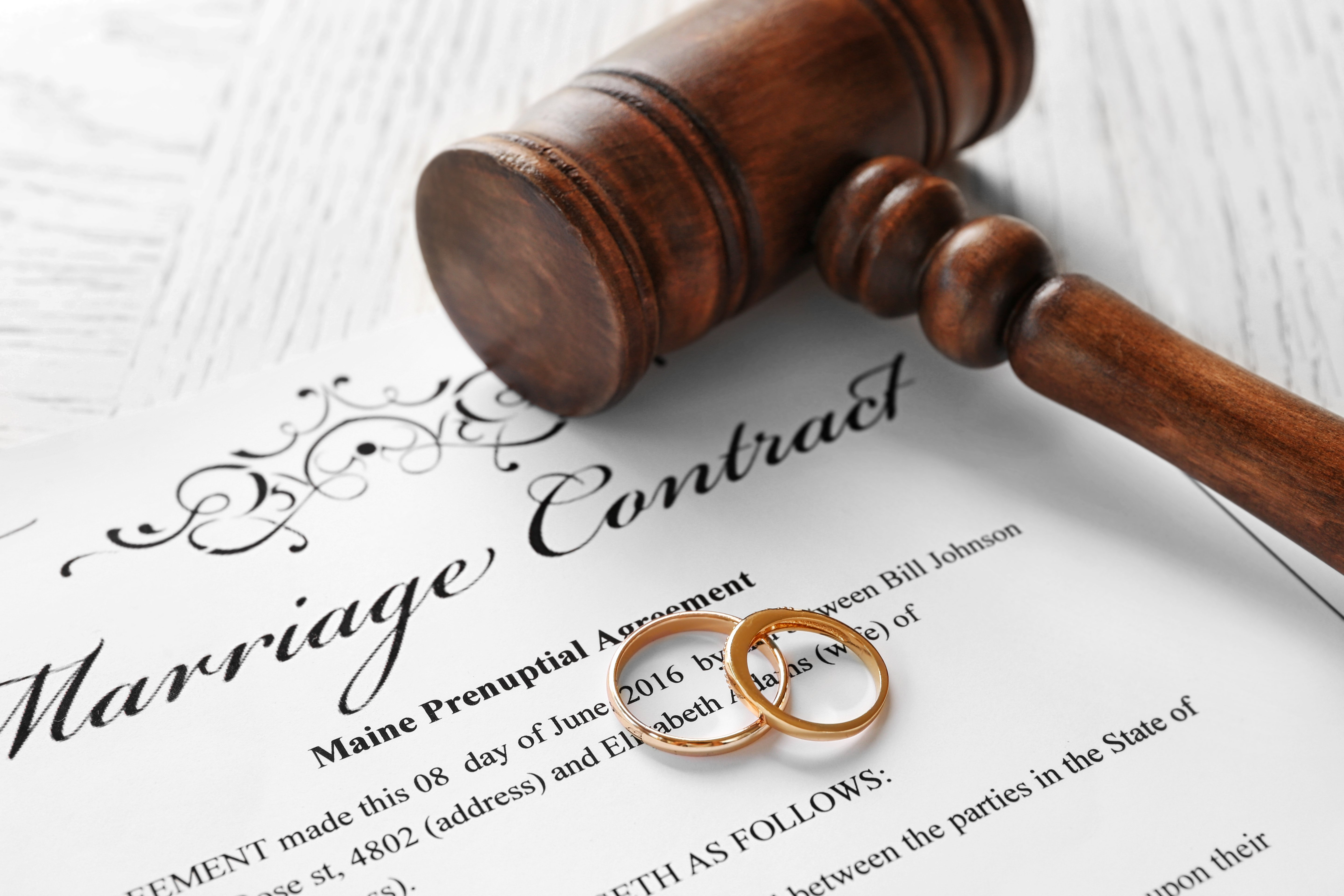 Golden wedding rings with judge gavel on marriage contract. | Photo: Shutterstock