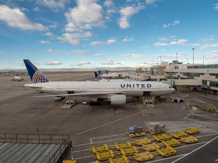 A United Airlines Boeing 777-200 at Denver International Airport with two open cargo holds ready to load nearby in Denver, Colorado   Photo: Myra Thompson via Shutterstock