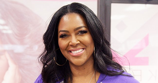 See Kenya Moore Show off Her Fit Figure in a Tight Orange Dress While Posing for a Photo Shoot