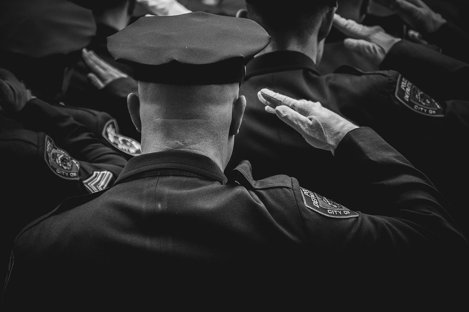 A black-and-white picture of police officers giving a hand salute to their fallen colleague. | Photo: Pixabay