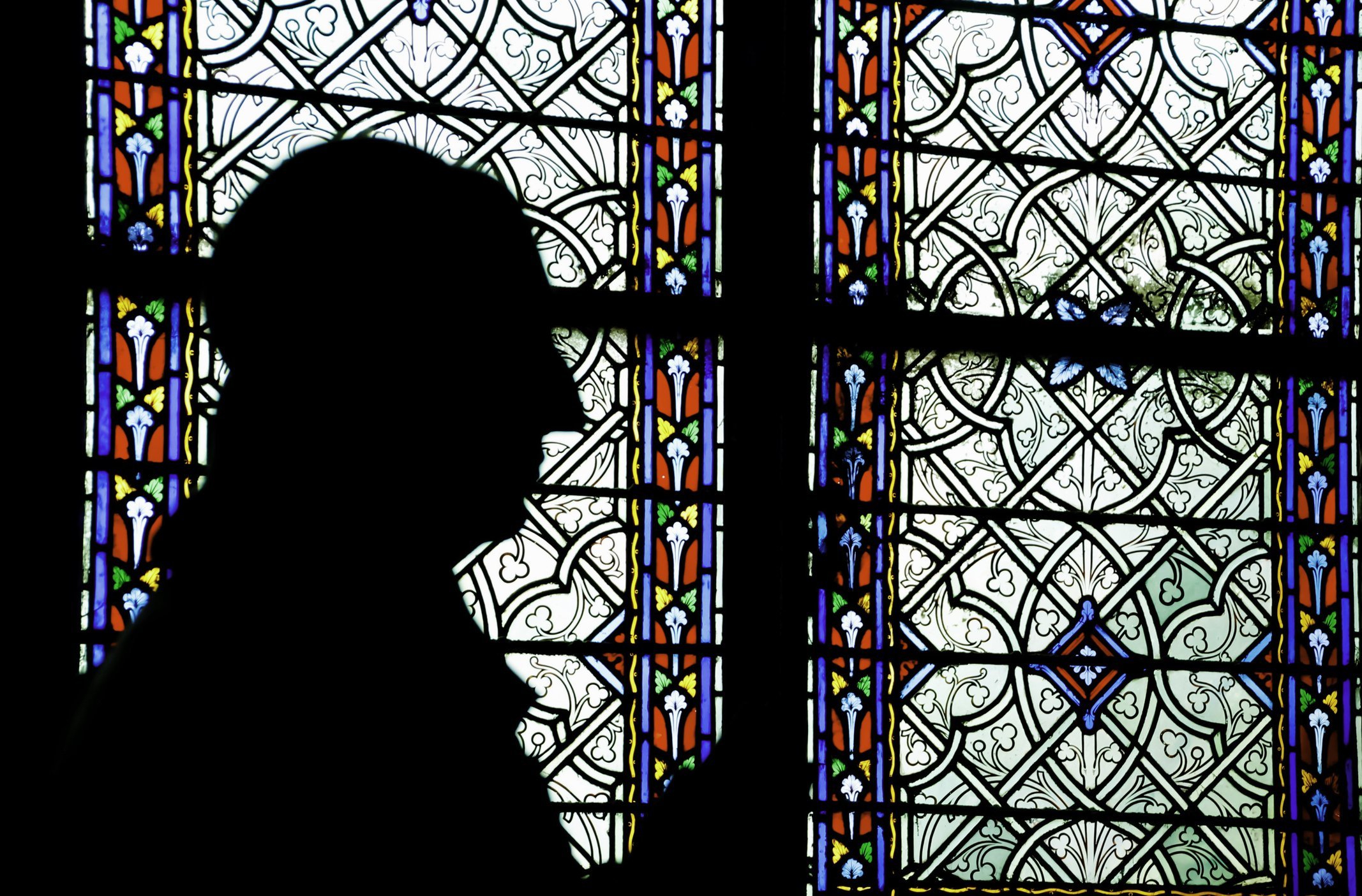 Man praying in front of stained glass window in church | Photo: Getty Images