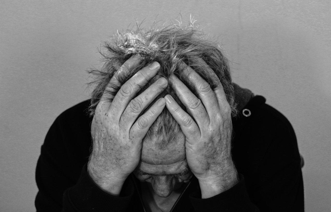 Un homme avec des mains sur la tête. | Photo : Pxhere