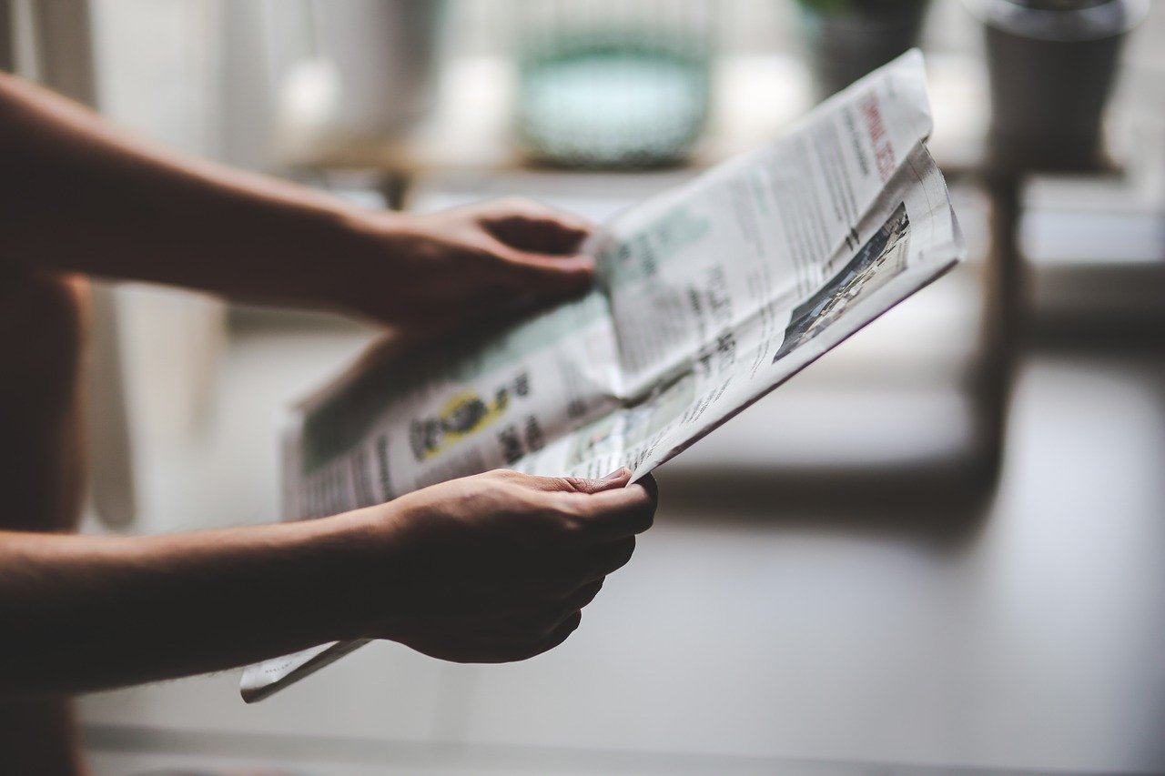 Someone holds an open newspaper in front of them | Photo: Pixabay