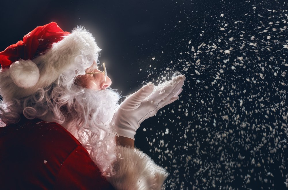 Santa Claus pictured blowing snow into the air. | Photo: Shutterstock