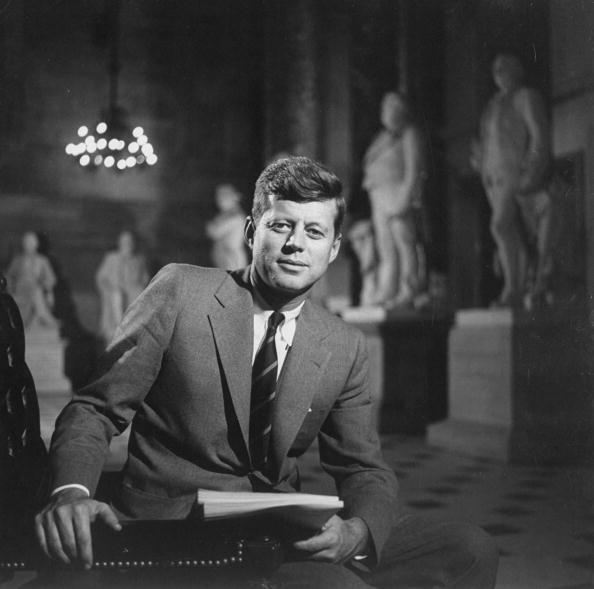 Photo of Senator John F. Kennedy seated in a museum with statues | Photo: Getty Images