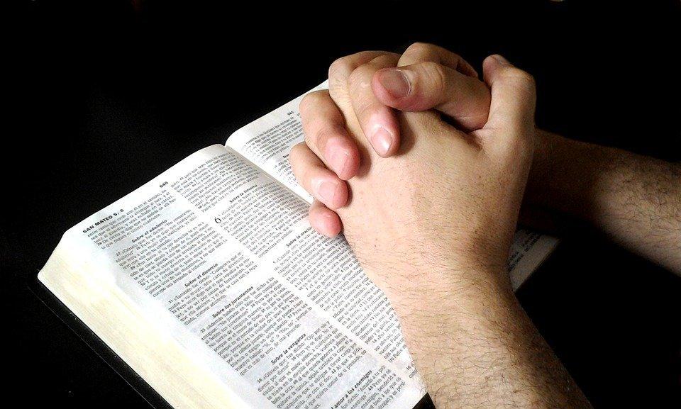 Persona rezando junto a la biblia. | Foto: Pixabay