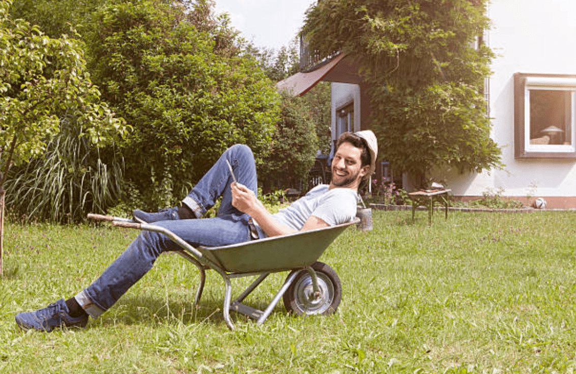 Smiling man lays in a wheelbarrow in a garden | Source: Getty Images