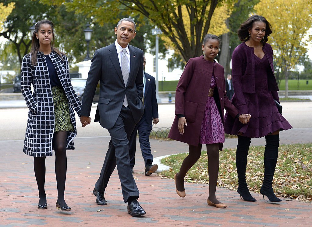 President Barack Obama walks with his wife Michelle Obama (R) and two daughters Malia Obama (L) and Sasha Obama (2R) through Lafayette Park to St John's Church to attend service | Photo: Getty Images