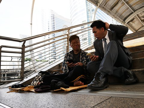 Photo of a business man and homeless man sitting by the street   Photo: Getty Images