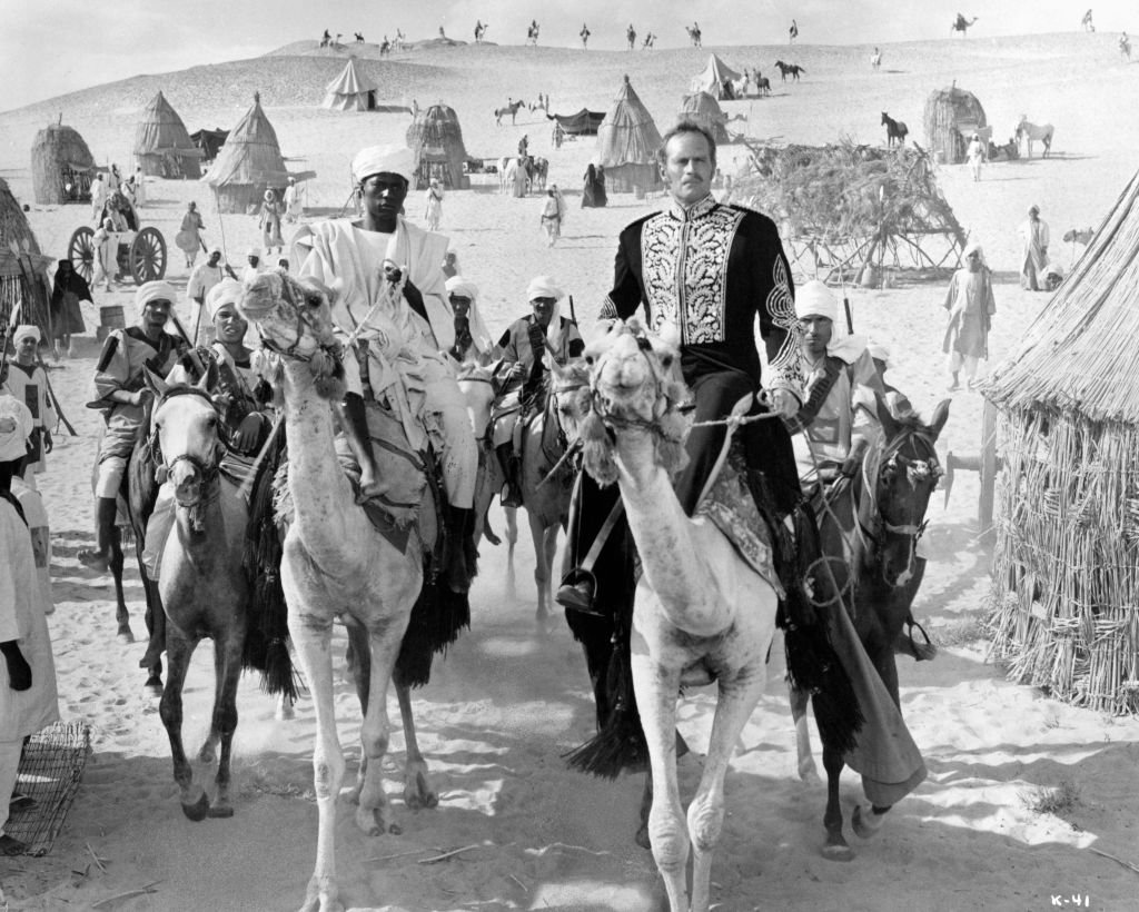 Charlton Heston and Johnny Sekka riding a camel with a group of men behind him riding horseback in a scene from the film 'Khartoum', 1966. | Photo: Getty Images