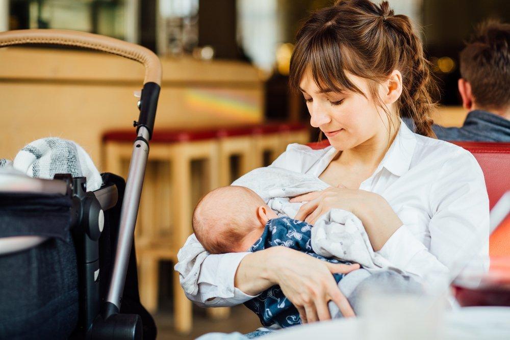 Una joven madre amamantando a su bebé en un café mientras está tomando un té. Fuente: Shutterstock