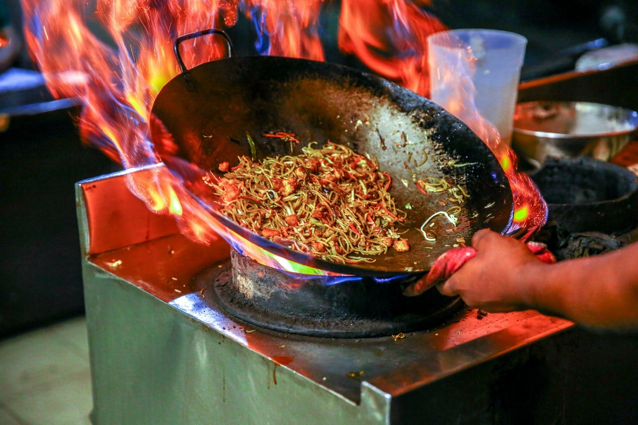 Person making noodles in a wok | Source: Pexels