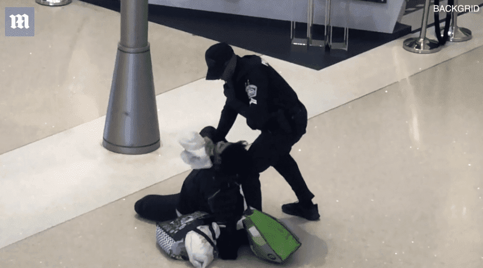 A woman is pined to the ground by a police officer at LAX | Photo: Daily Mail/BackGrid