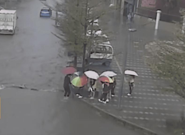 Maestra cargando a sus alumnos sobre una calle inundada en China. | Imagen: YouTube/Daily Mail