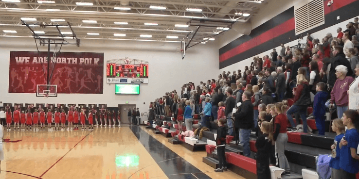 Audience standing and singing the National Anthem ant North Polk | Photo: WHO TV Channel 13 News