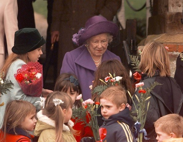 The Queen Mother (centre) is assisted by her great-grandaughter Princess Beatrice (left) as she recieves flowers from children after the Christmas Day Church Service at the Sandringham Estate. * The Royal family traditionally spend the Christmas period on their estate in Norfolk, eastern England | Photo: Getty Images