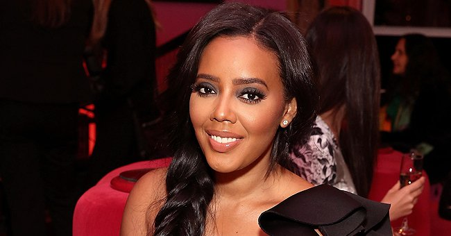 Angela Simmons Shows Toned Legs in White High Heels & a Cleavage Revealing Peach Pleated Dress