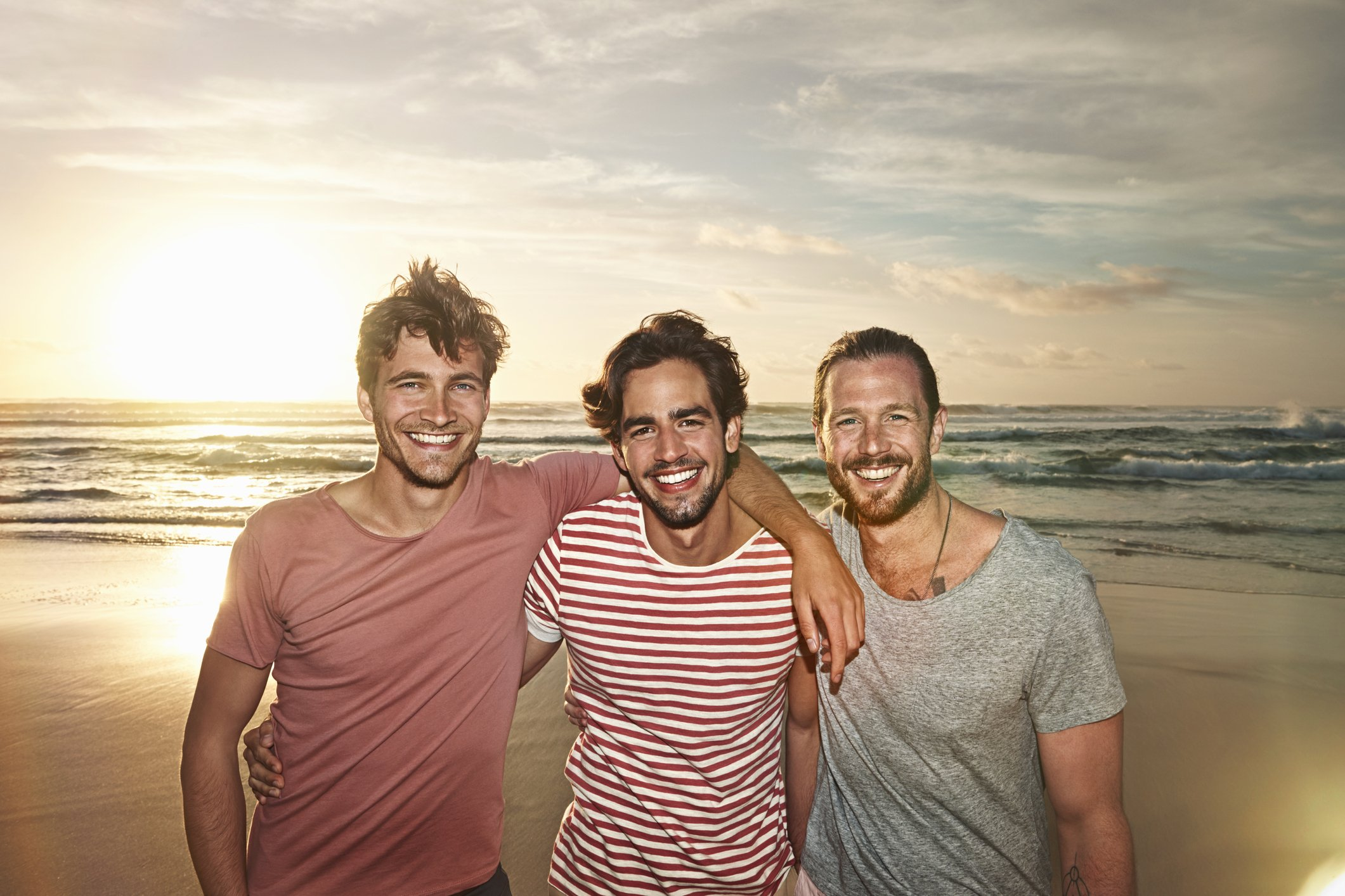 Three male friends on the beach smiling.   Photo: Getty Images