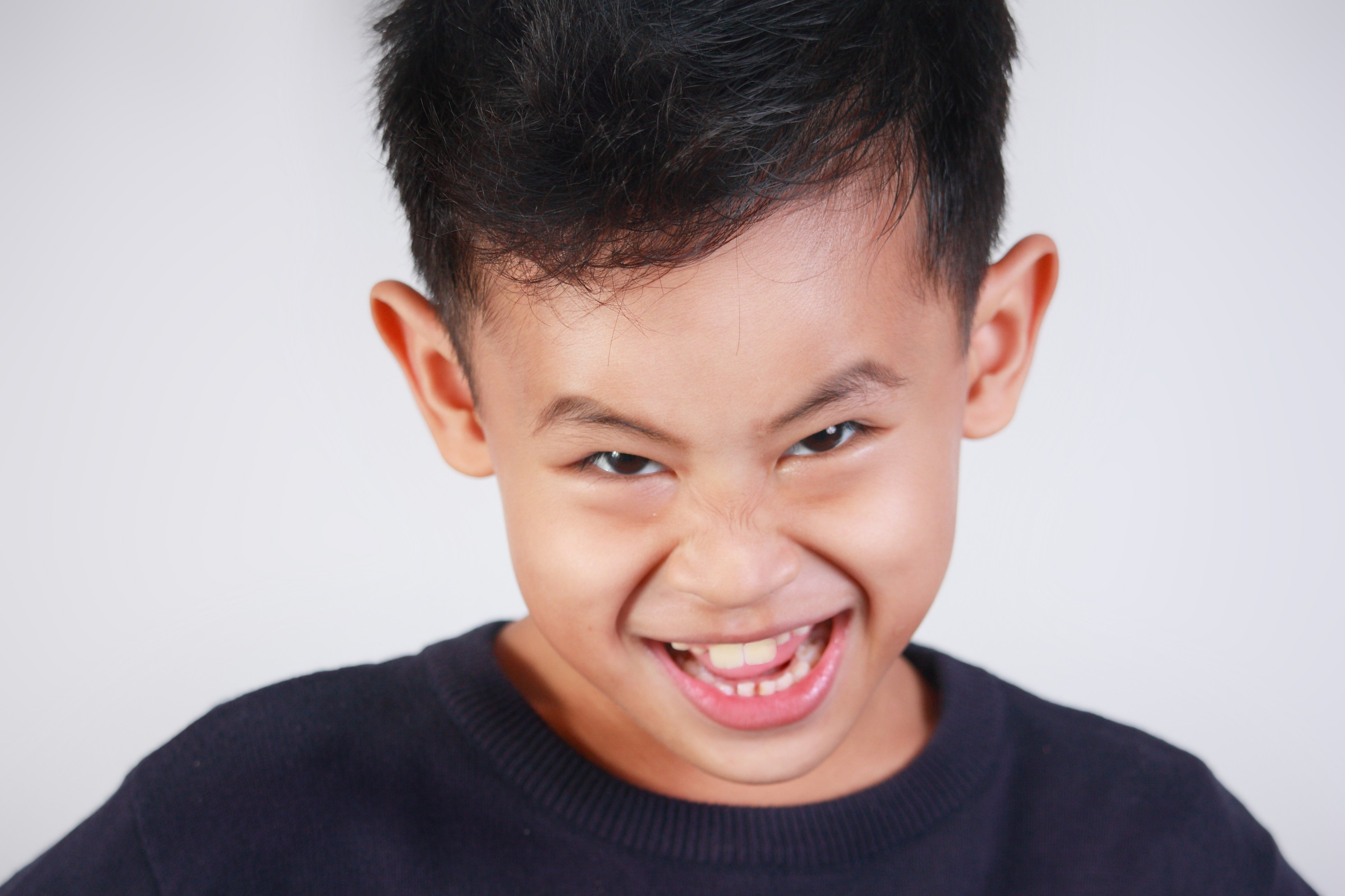 Dark haired boy with naughty facial expression. | Source: Shutterstock