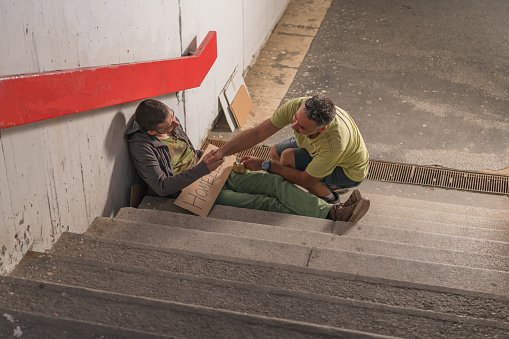 A polite and kind man is pictured helping a homeless person who is sitting on the stairs in the city underground   Photo: Getty Images