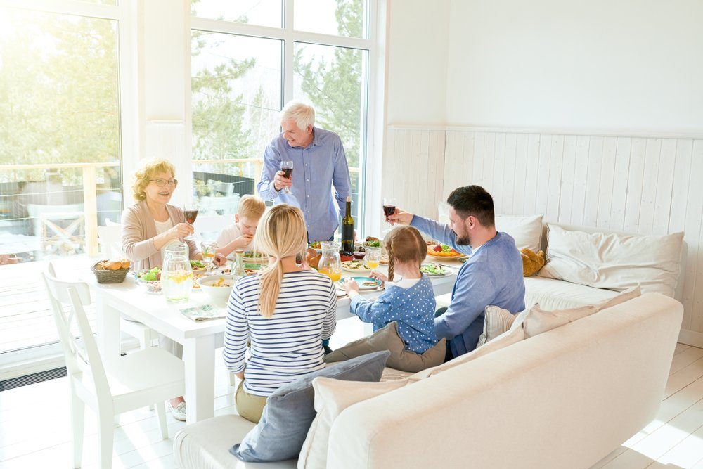 Portrait of happy two generation family enjoying dinner together sitting at festive table | Photo: Shutterstock