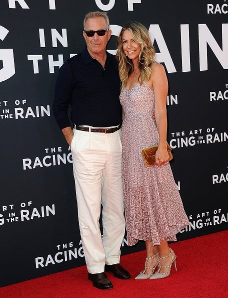 """Kevin Costner and Christine Baumgartner arrive for the Premiere Of 20th Century Fox's """"The Art Of Racing In The Rain"""" held at El Capitan Theatre 