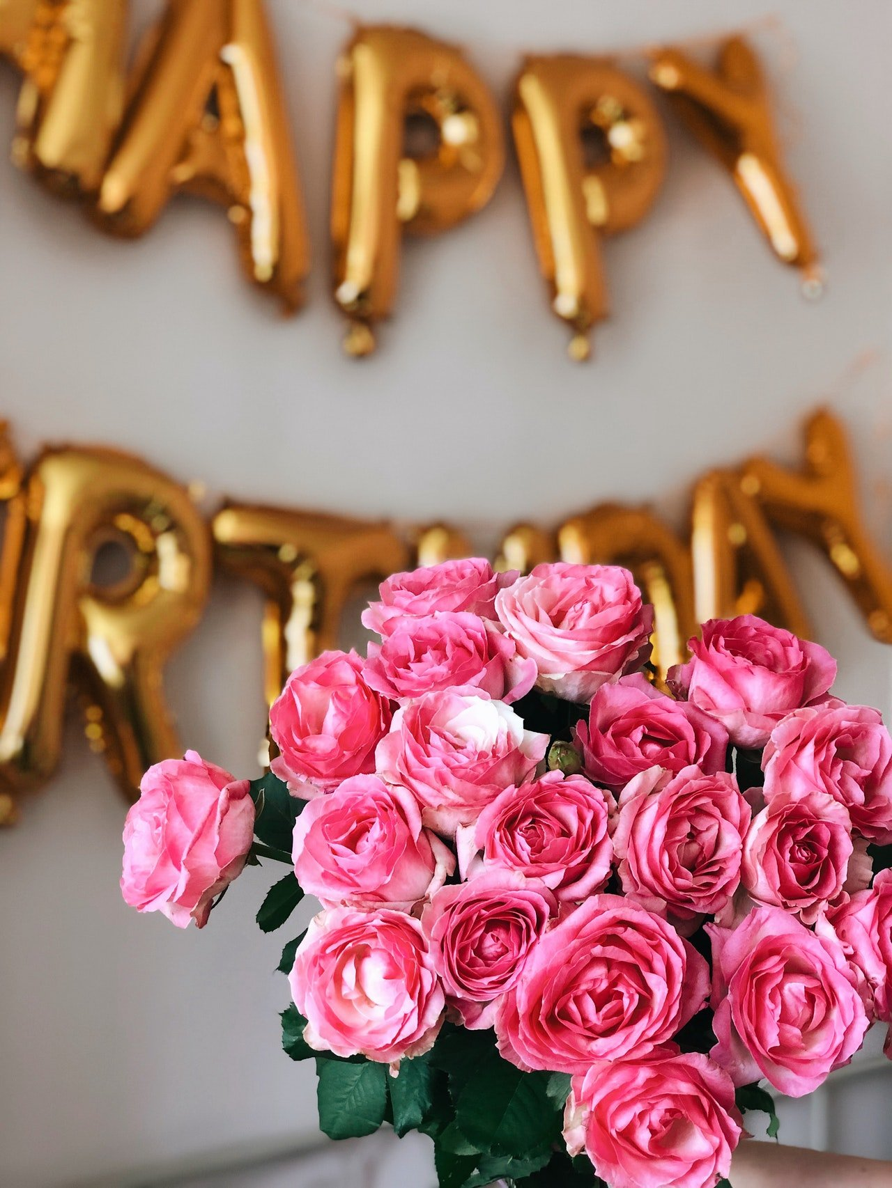 Beautiful flowers with birthday balloons in the background | Photo: Pexels