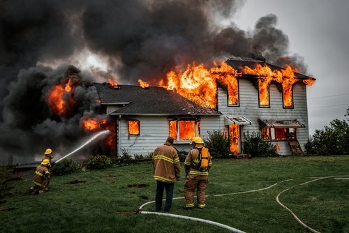 Firefighters putting out a house fire.| Photo: Shutterstock.