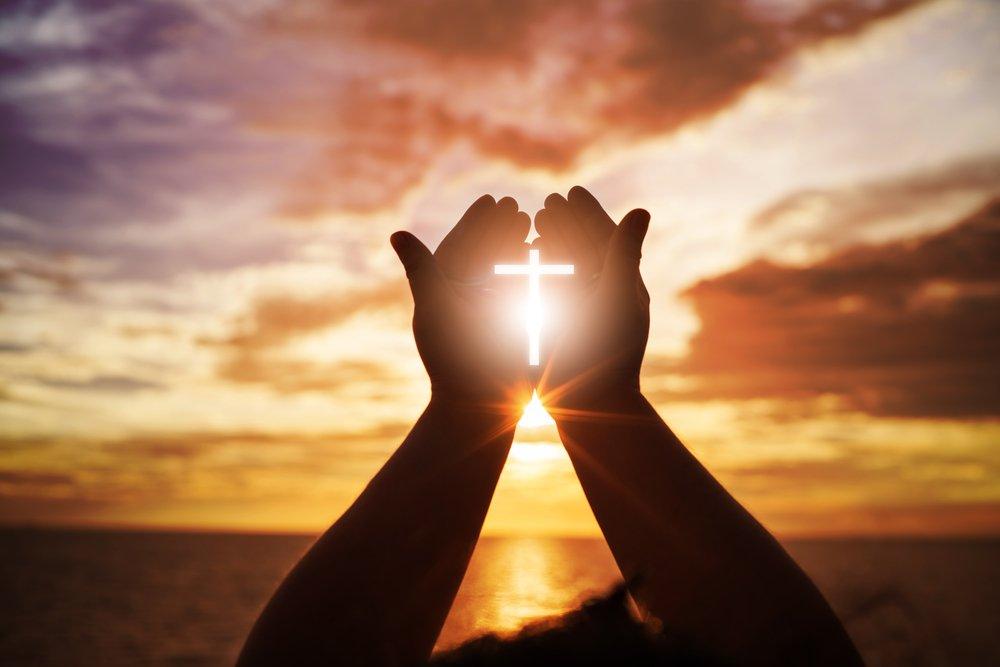 Manos en adoración con cruz en el medio.| Fuente: Shutterstock