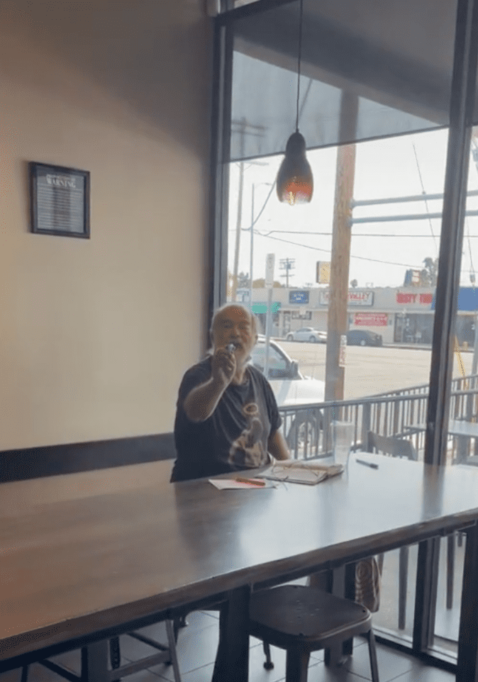 An older man sitting at the table compliments a Starbucks customer in the store | Photo: TikTok/rosette_luve