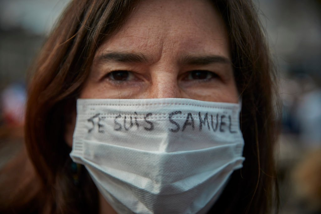 "Une manifestante porte un masque avec le slogan ""Je Suis Samuel"". 