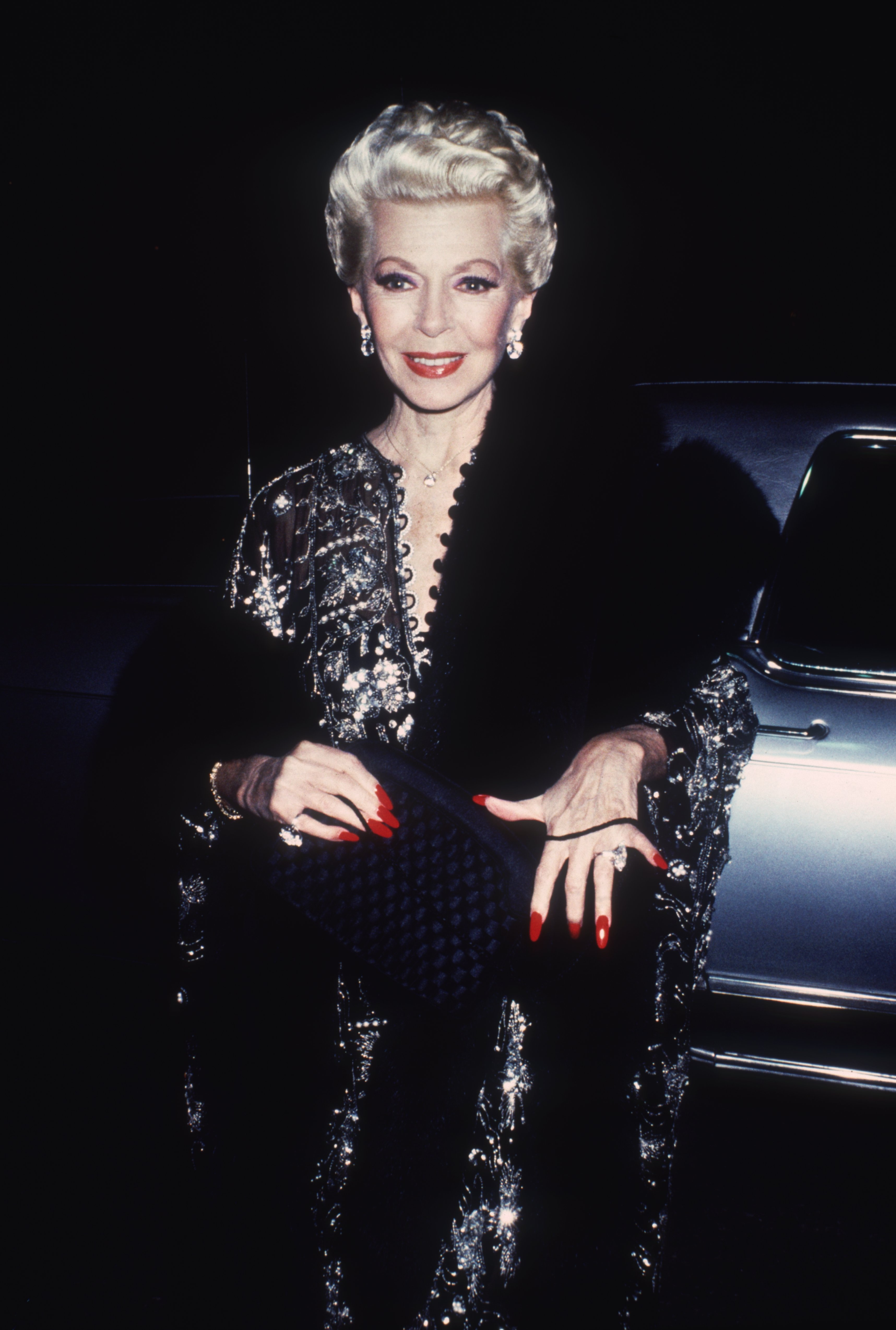 18th December 1984: American actor Lana Turner (1921 - 1995) with platinum blonde hair and red lips and nails, smiles while arriving for a party for the TV show, 'The Love Boat' aboard the Princess Cruise Line's ship 'Royal Princess,' Los Angeles, California. | Source: Getty Images