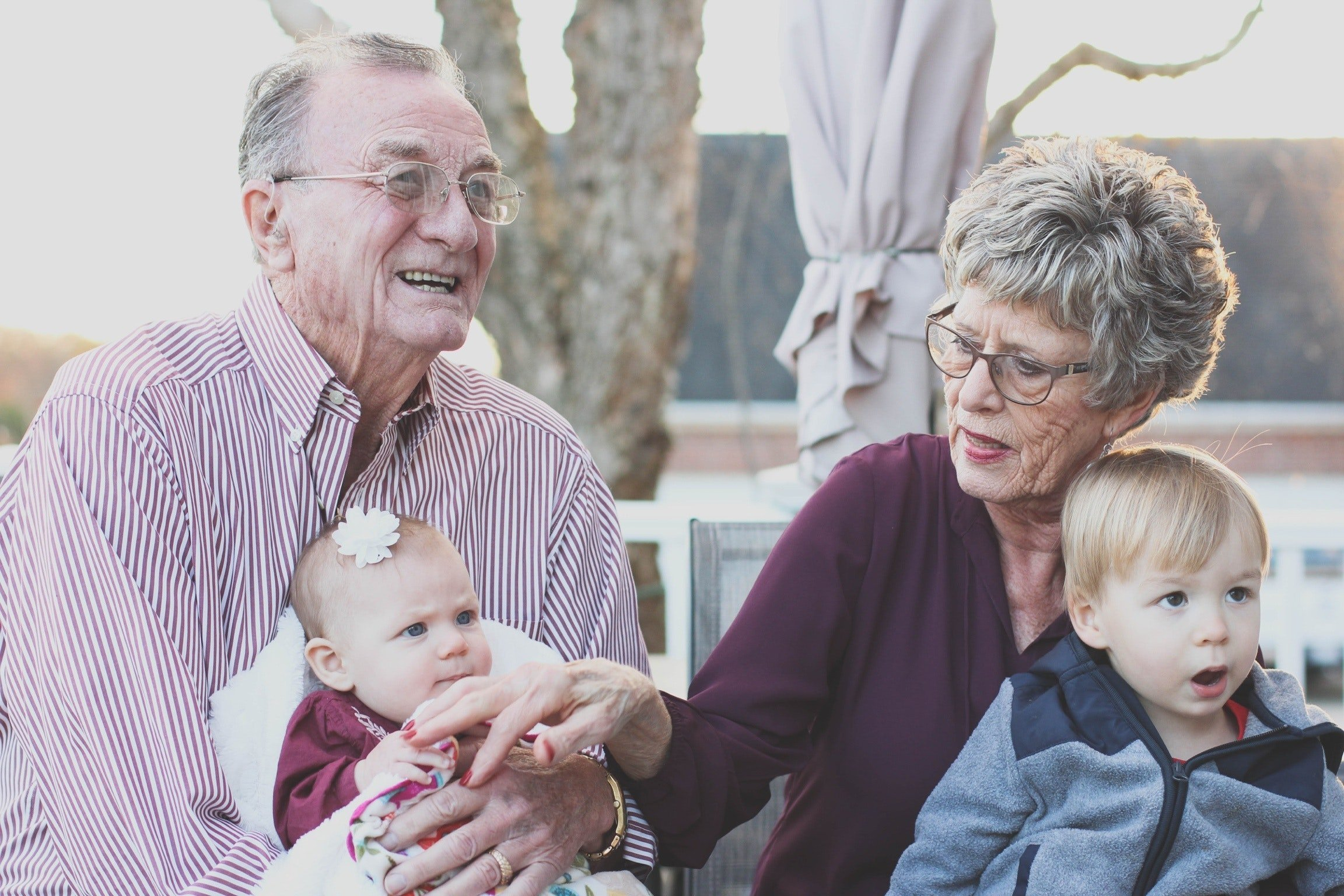An elderly couple with two toddlers | Source: Pexels.com