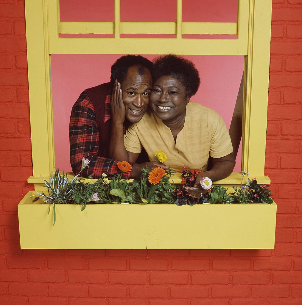 John Amos and Esther Rolle pose behind a flowerbox on a windowframe for the television show 'Good Times,' Los Angeles, California, mid to late 1970s | Photo: GettyImages