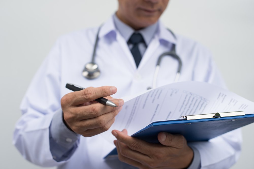 Male doctor in white coat looking over medical documents.| Source: Shutterstock
